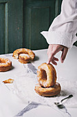 Boy's hand hold homemade puff pastry deep fried donuts or cronuts with sugar