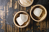 Empty gua bao steamed buns in opened bamboo steamer over dark wooden plank background