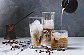 Iced coffee cocktail or frappe with ice cubes and pouring cream in three different glasses with vintage jezva and coffee beans around on white marble table