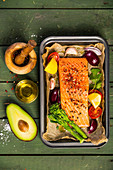 Baking dish with fresh raw salmon steak, vegetables and seasonings on green wooden background