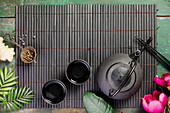 Asian food background - tea and chopsticks on dark rustic background