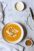 A bowl of thick homemade pumpkin soup with small bowls of cream and nutmeg and chives