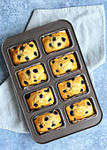 Individual blueberry loaf cakes cooling in a tin
