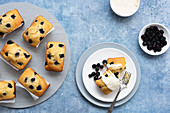 Individual blueberry loaf cakes with a serve on a plate and a bowl of blueberries and a bowl of cream