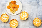 Small lemon tarts with a plate of candied orange, lime and lemon slices