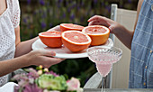 Two women sitting at an outdoor brunch, one woman passing a tray of grapefruit halves and the other woman reaching for one
