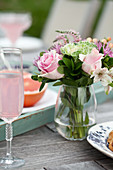 Brunch outside, flowers, glasses of sparkling pink lemonade, grapefruit halves on an outdoor table