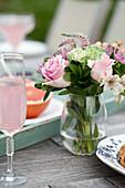 Gedeckter Tisch zum Brunch mit Blumen, rosa Limonade und Grapefruithälften