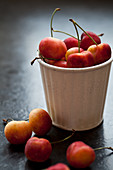 A white tin cup filled with Rainier cherries on a black countertop
