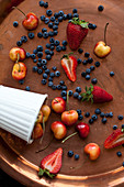 Rainier cherries, strawberries and wild blueberries on a copper tray and in a white tin cup