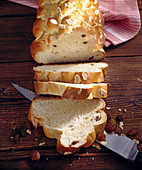 Sliced Bohemian bread with a knife on a wooden background