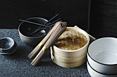 Soba noodles, bamboo steamer and asian cuisine props on dark background