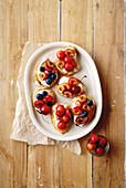 Bruschettas with cherry, blueberry, honey sauce and cream cheese