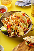 Close up of mexican tacos with chili con carnes and grated cheese served over a yellow background