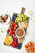 Verschiedene Früchte mit Schokosauce, Käse, Crackern und Nüssen auf Servierbrett