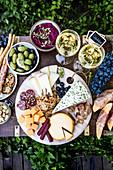 Vorspeisenplatte im Freien mit Käse und Wurst serviert mit Dip, Oliven, Obst und Wein