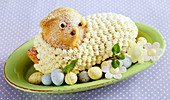 Baked Easter lamb bread with a buttercream coat, on an oval plate with sugar eggs
