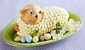 Gebackenes Osterlamm mit Buttercreme-Fell auf ovalem Teller mit Zuckereiern