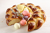 A yeast wreath for Easter breakfast with colorful easter eggs and catkins