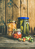 Autumn seasonal pickled vegetables and fruit in glass jars, rustic wooden barn background