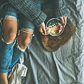 Woman in sweater and jeans eating rice coconut porridge with figs, berries, hazelnuts