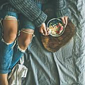 Gesundes Winterfrühstück: Frau isst Reis-Porridge mit Kokos, Feigen, Beeren und Nüssen