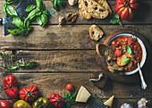Tomaten-Knoblauch-Suppe auf Holzbrett mit Basilikum, Brot und Parmesan (Italien)