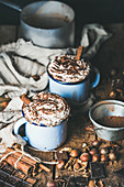 Hot chocolate in blue mugs with whipped cream and cinnamon sticks, spices, nuts and cocoa powder