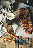 Roasted pork ribs with garlic, rosemary and glass of dark beer