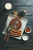 Grilled sausages with sauces and glass of dark beer on rustic wooden serving board