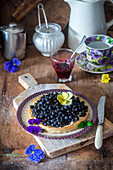 Blueberry tart decorated with edible flowers