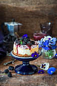 A mini blackberry cheesecake with blackberry sauce and edible flowers