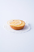 A mini tartlet with lemon cream against a white background