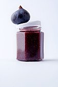 A jar of fig jam against a white background