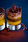 Layered dessert in glasses with orange and chocolate mousse