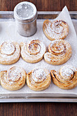Cinnamon rolls with icing sugar on a baking tray