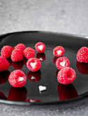 raspberries with sugar hearts on a black plate