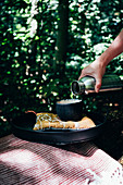 A cup of tea at a tray in the woods, a hand is pouring tea in a cup