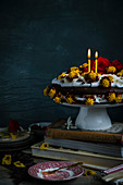 A cake with merengue and chocolate cake with eatable flowers with candles standing on books
