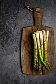 Asparagus with a little red rope on a wooden plank at a black canvas