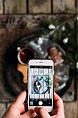 Foto mit Handy von einer Tasse Tee mit Weihnachtsplätzchen