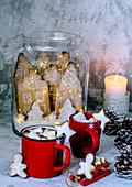 Heiße Schokolade mit Marshmallows und Lebkuchenhäuser mit Lichterkette im Glasgefäss
