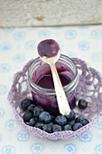 Blueberry curd in a glass with a spoon