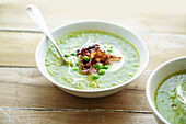 Creamy green pea soup with fried bacon and herbs