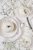 weiße Kürbisse und Miniauberginen als Tischdeko