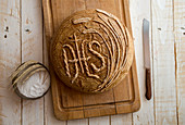 Farmhouse bread decorated with IHS lettering and corn