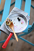 A small frying pan with the remains of blueberry crumble on a spatula