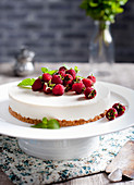 Goat cheese cheesecake with fresh raspberries and mint leaves on top