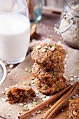 Oat and peanut butter cookies with pumpkin seeds and cinnamon with a glass of milk.