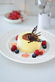 Quark tart with a chocolate butterfly and berries